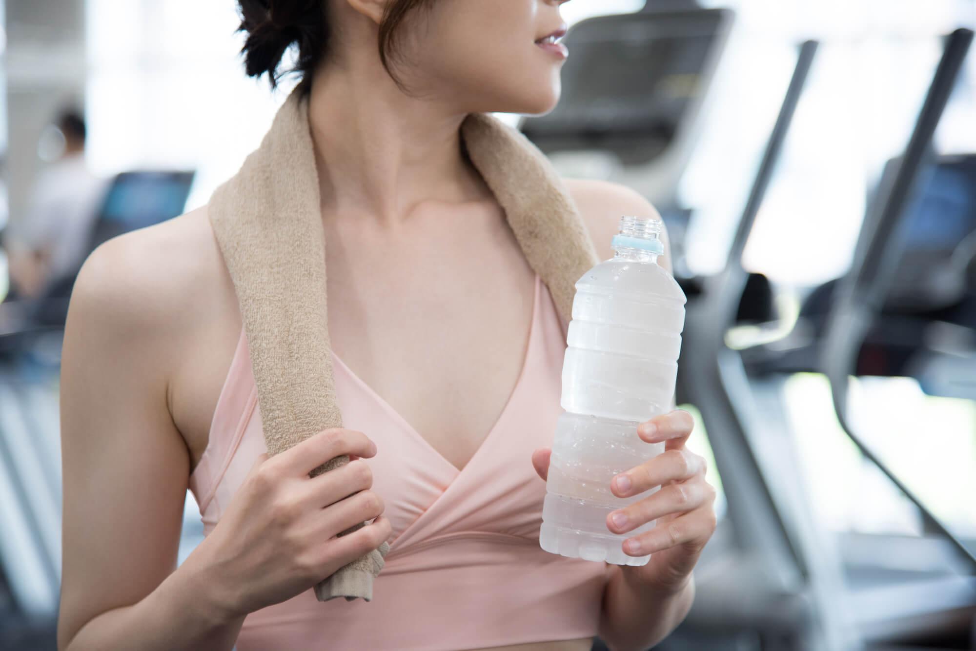 筋トレ後にサプリメントを飲む女性