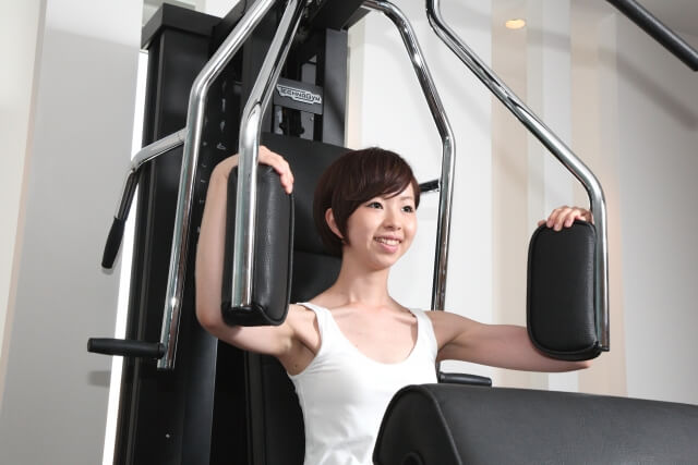 ジムのマシンでトレーニングメニューを楽しむ筋トレ初心者の女性